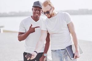 Dos jóvenes amigos multiétnicos hablando entre sí y sonriendo mientras foto