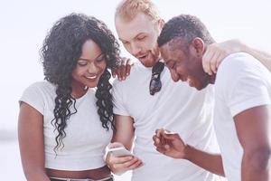 Group of multiracial happy friends using gadget outdoors. Concept of happiness and multi ethnic friendship all together against racism photo