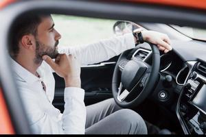 Confident young businessman sitting at the wheel of his new car photo