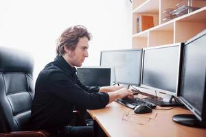 Male programmer working on desktop computer with many monitors at office in software develop company. Website design programming and coding technologies photo