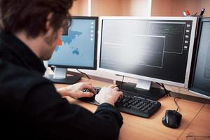 The young dangerous hacker breaks down government services by downloading sensitive data and activating viruses. A man uses a laptop computer with many monitors photo