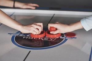 Manos de jóvenes sosteniendo el delantero en la mesa de hockey de aire en la sala de juegos foto