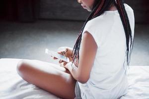 retrato de mujer hermosa que se despierta en su cama y mira en el teléfono. consultar redes sociales, enviar sms. la niña lleva una camiseta foto