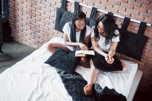 Two beautiful african girl in sleepwear smiling sitting on bed at home woke up in the morning on a sunny day. photo