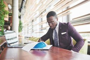 un joven empresario firma un contrato en una sala de conferencias foto