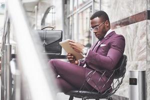 un hermoso empresario afroamericano lee un menú en un café foto