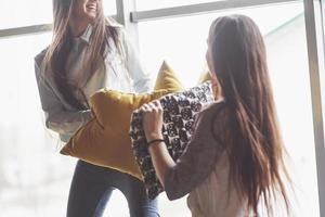 dos hermosas hermanas gemelas jóvenes pasan tiempo juntas y están luchando con almohadas. hermanos que se divierten en el concepto de casa foto