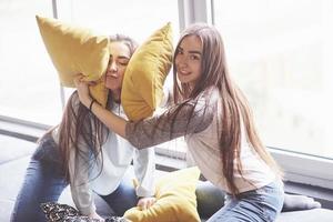 dos hermosas hermanas gemelas jóvenes pasar tiempo juntos con almohadas. hermanos que se divierten en el concepto de casa foto