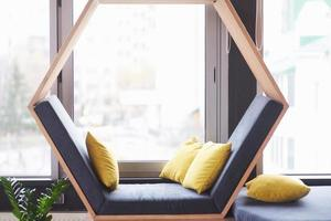 office lounge interior office building or cafe, sofa chair in the form of a hexagon with pillows near the window photo