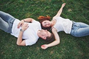 Cheerful couple lying on the grass. Young people outdoors. Happiness and harmony. photo