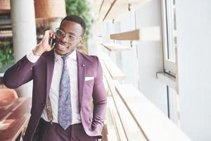 Portrait of a young and handsome African American businessman talking in a suit over the phone photo