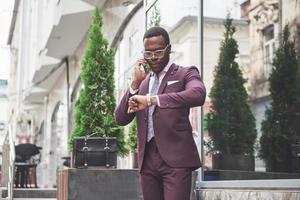 Retrato de un joven y guapo empresario afroamericano hablando en un traje por teléfono. preparándose para una reunión de negocios. foto