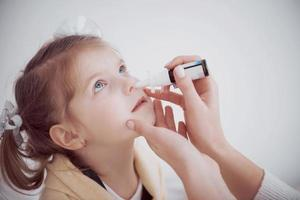 the girl drips into her nose with a spray of cold photo