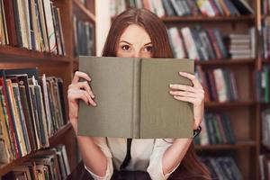 Young attractive student librarian reading a book between library bookshelves photo
