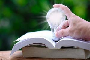 Idea innovation and inspiration concept, illuminated light bulb on book, Innovation, brainstorming, inspiration and education concepts. photo