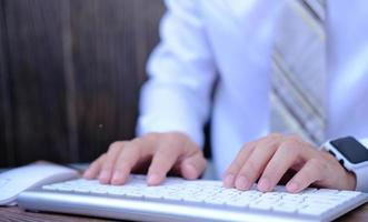 Businessman working on computer in office, typing keyboard photo