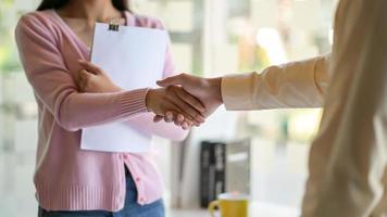 hombres y mujeres se dan la mano para trabajar juntos. foto