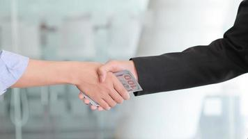 Handshaking and having money in hand for corruption. photo
