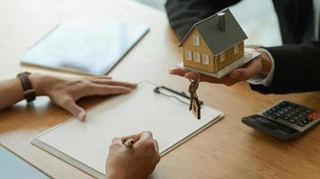 House broker is introducing the client to sign the purchase contract. photo