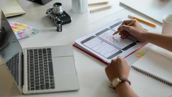 El diseñador está dibujando una pantalla de teléfono inteligente para futuros clientes en el escritorio con computadora portátil y artículos de papelería. foto