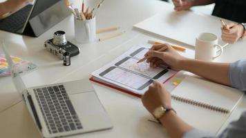 Toma recortada del joven equipo de diseñadores de ux que trabaja en un proyecto de aplicación para teléfonos inteligentes con tableta digital en la sala de la oficina moderna. foto