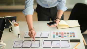Toma recortada del joven diseñador de ux que trabaja en un nuevo proyecto de aplicación mientras usa un teléfono inteligente en la sala de la oficina moderna. foto