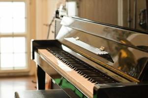 Cropped shot of Classical piano in a room with natural light through beautiful window. photo