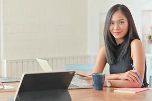 A portrait of a beautiful asian businesswoman with a laptop sitting in her comfortable office. photo