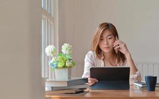 Female college student studying online at home is using a smartphone for advice from an instructor. photo