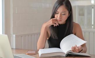 las mujeres jóvenes están leyendo libros para el examen de ingreso a la universidad en la sala de estar de su casa. foto