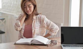 Primer plano de una chica universitaria leyendo un examen final en la sala de estar de casa. foto