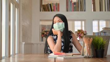 jóvenes estudiantes usan una máscara y miran por la ventana. ella prepara sus exámenes en el hogar para protegerse contra el virus coronario o covid-19. foto