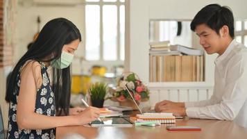niñas con máscara y hombres sin máscara que trabajan en un café. él y ella corren el riesgo de infectarse con el virus covid-19. foto