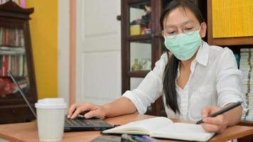 Asian woman is taking notes and using a laptop. She works at home to protect against the Corona virus or Covid-19. photo