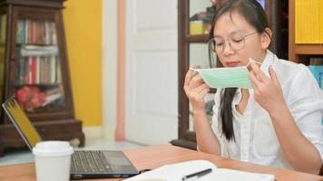 Asian woman is wearing a mask. She works at home to protect against Corona virus or Covid-19. photo
