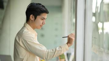 Young business man is taking notes working on a note on a glass wall in a modern office. photo