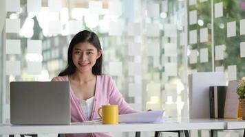 una joven estudiante con una computadora portátil y un café, está trabajando en un proyecto para graduarse. foto