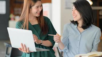 Young business women use laptop to discussing the project together in  modern office with good emotions. photo