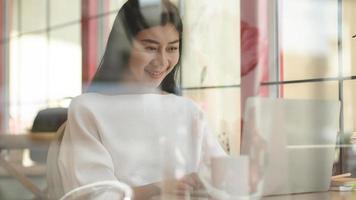 niña usa una computadora portátil para una videoconferencia en un café, tomada desde el exterior a través del vidrio. foto