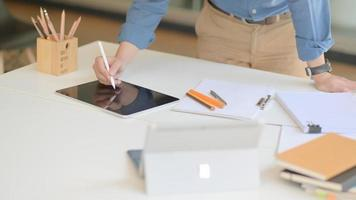 A professional designer is working on a modern tablet to design his future project in a comfortable office. photo