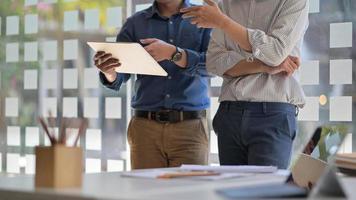 dos hombres asiáticos usando una tableta. se colocan para consultar el trabajo para presentar a los clientes en la oficina contemporánea. foto