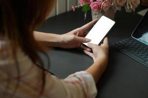 mujer joven con un teléfono inteligente en la mano para buscar información y una computadora portátil en el escritorio de la oficina. foto