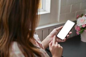 La vista de primer plano de la mano de una mujer está utilizando un teléfono inteligente con pantalla en blanco para buscar información sobre su proyecto. foto