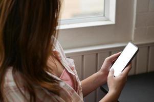 primer plano de una mujer joven con un teléfono inteligente en la mano para buscar información. foto