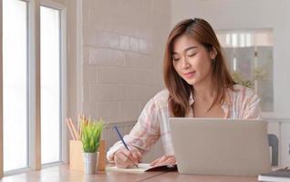 estudiante adolescente está tomando notas y estudiando en línea en casa con una computadora portátil. foto