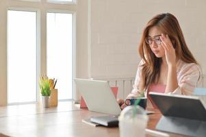 estudiante mujer asiática, sosteniendo las gafas con cuidado mientras mira la computadora portátil para prepararse para estudios de posgrado. foto
