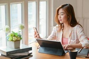 A portrait of a Asian female student is using a smartphone and a laptop to prepare for university graduation. photo