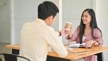 foto de hombres dando café a mujeres mientras están estresados leyendo libros para la preparación de exámenes.