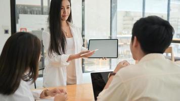 El equipo de hombres y mujeres jóvenes presenta un nuevo plan de proyecto en tableta en una oficina moderna. foto