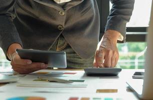 concepto de un nuevo empresario está utilizando tabletas y calculadoras en la oficina. foto